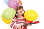 happy little girl with guitar and balloons birthday party